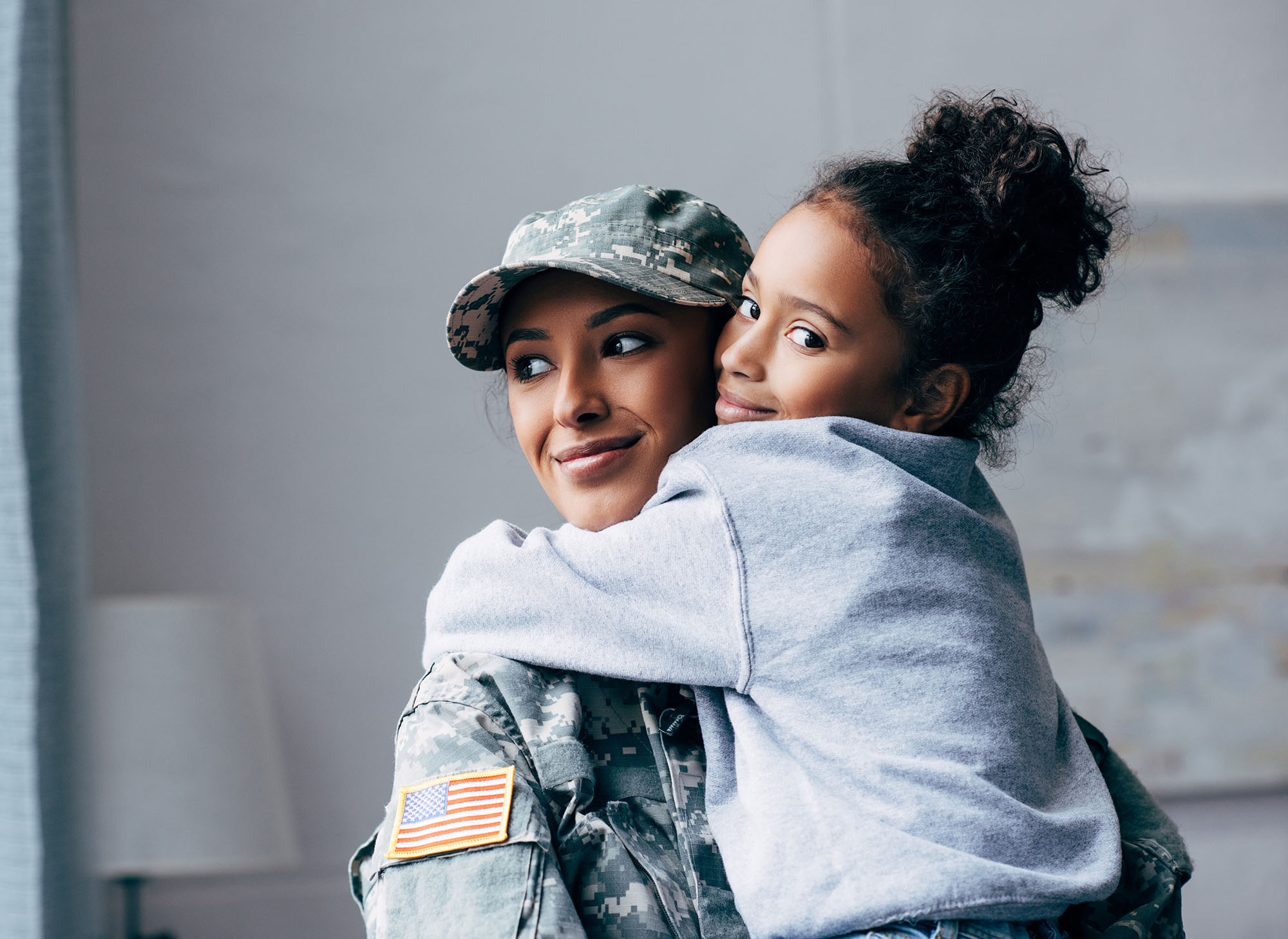 Army woman hugging girl